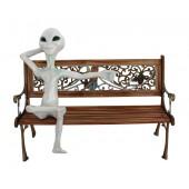Alien auf der Bank mit ausgestrecktem Arm