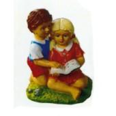 Junge und Mädchen sitzend mit Buch auf Wiese