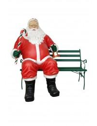 sitzender dicker Weihnachtsmann auf Bank mit Glocke und Zuckerstange