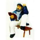 mittlelgroßer Seemann auf Bank mit Buch